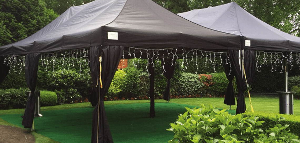 Black marquees in a garden with lights